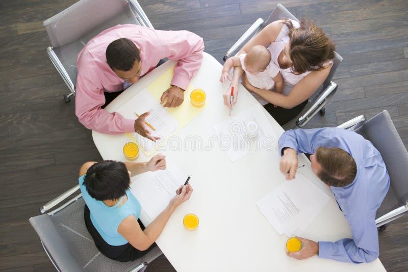 Quattro persone di affari in sala del consiglio con un bambino fotografia stock