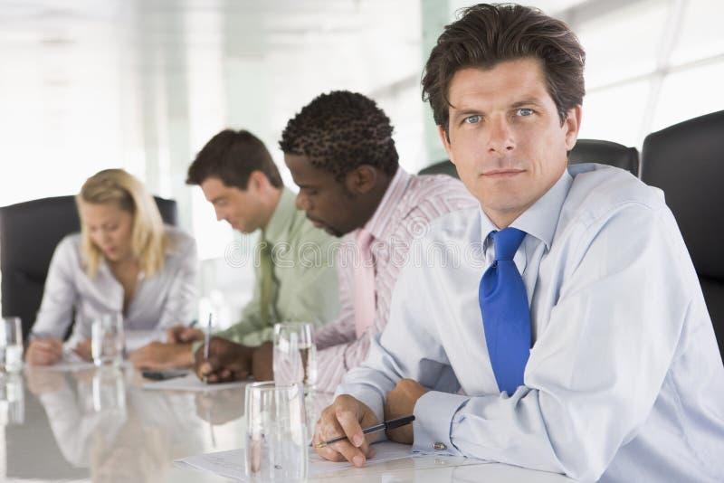 Quattro persone di affari in una scrittura della sala del consiglio immagine stock libera da diritti