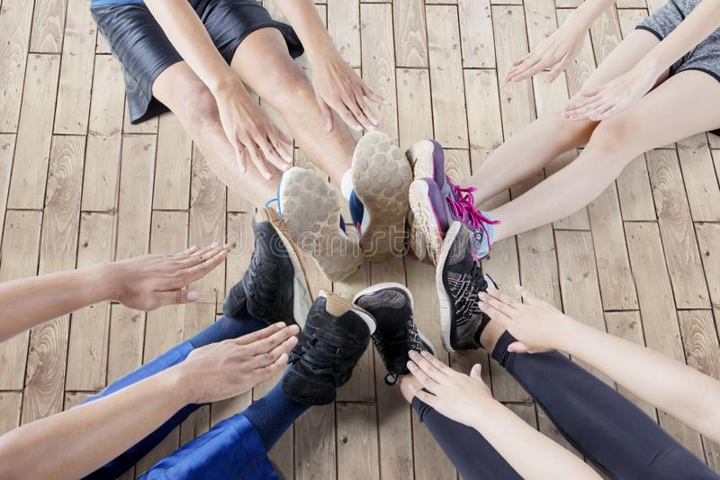 Quattro persone toccano i piedi sui pavimenti di legno immagini stock