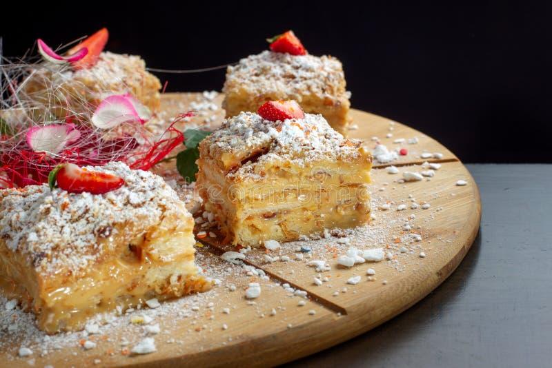 Quattro pezzi di millefoglie del dolce sul vassoio di legno Cucina russa, dolce stratificato con la crema di pasticceria fotografia stock libera da diritti