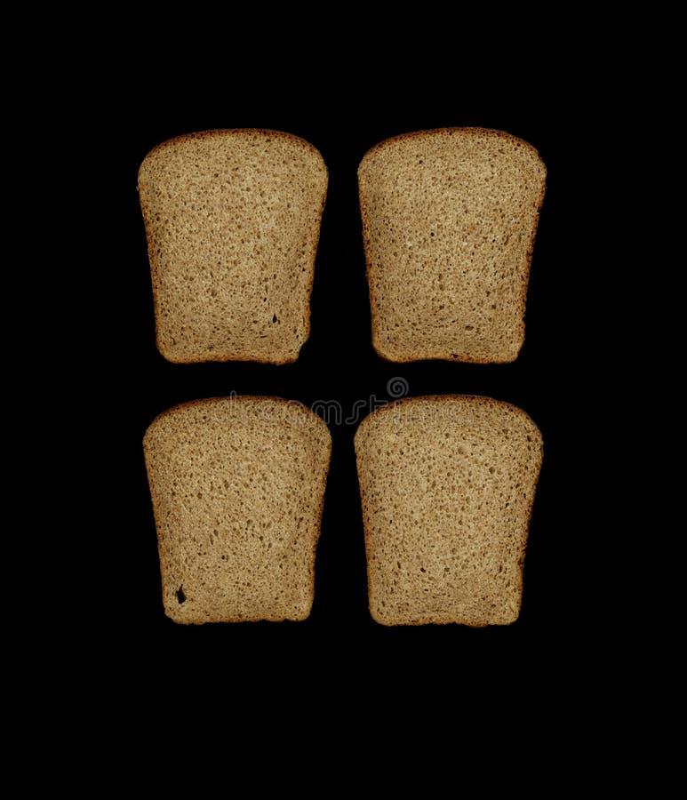 Quattro pezzi di pane di segale nero del lievito hanno tagliato da una pagnotta isolata su un fondo nero immagini stock libere da diritti
