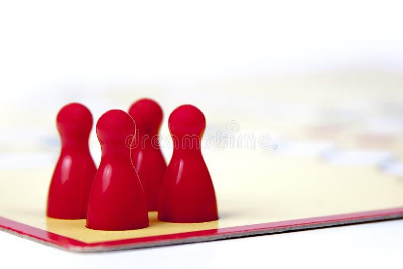 Quattro pezzi rossi del gioco su un bordo del gioco fotografia stock