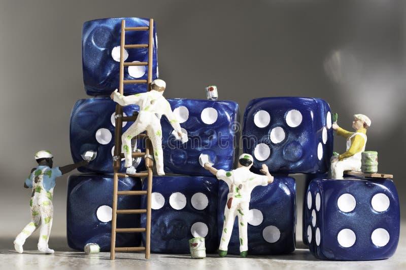 Quattro pittori miniatura della gente che dipingono i dadi blu con i semi bianchi immagini stock libere da diritti