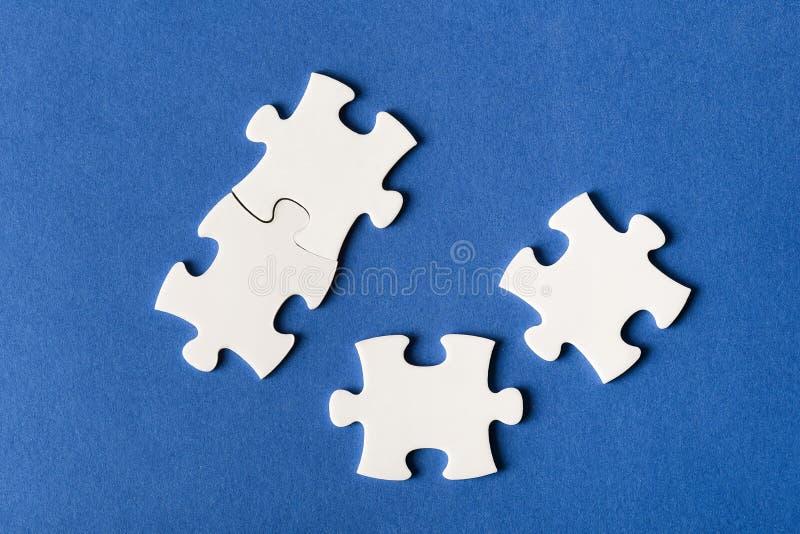 Quattro puzzle fissati dei colori differenti su fondo blu fotografie stock