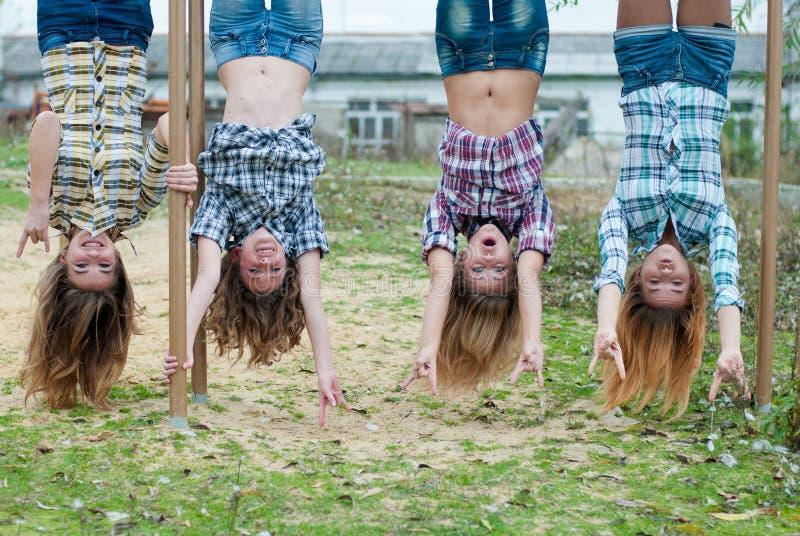 Quattro ragazze che appendono upside-down nella sosta immagine stock libera da diritti