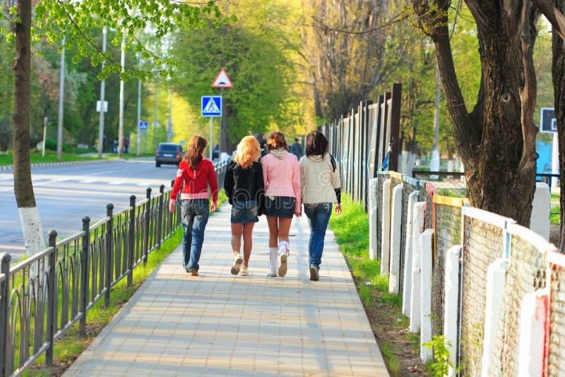 Quattro ragazze che camminano lungo la via fotografie stock libere da diritti