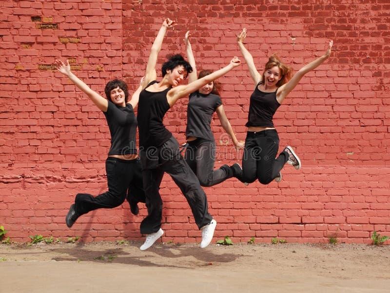 Quattro ragazze che saltano sulla priorità bassa della parete immagini stock libere da diritti