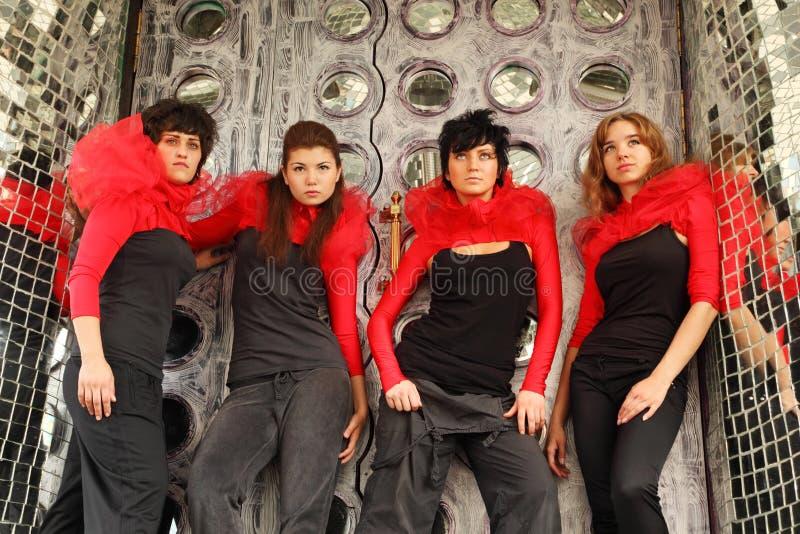 Quattro ragazze che si levano in piedi e che osservano in su fotografia stock libera da diritti