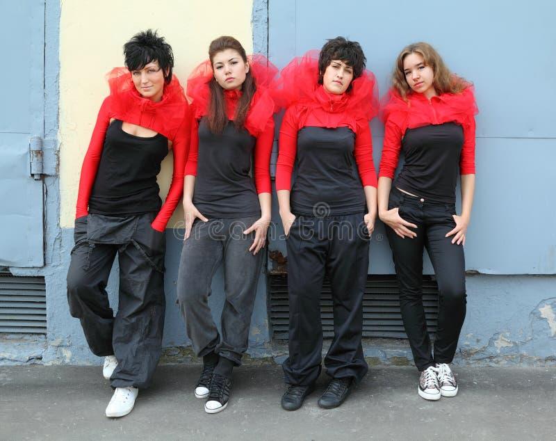 Quattro ragazze che si levano in piedi e che si appoggiano sulla parete immagine stock