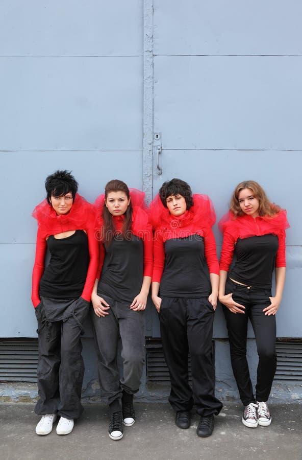 Quattro ragazze che si levano in piedi e che si appoggiano sulla parete fotografie stock