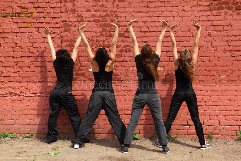 Quattro ragazze che si levano in piedi indietro e che sollevano le mani in su immagini stock