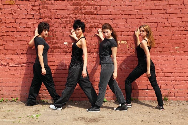 Quattro ragazze che si levano in piedi indietro e corpo di giro fotografie stock