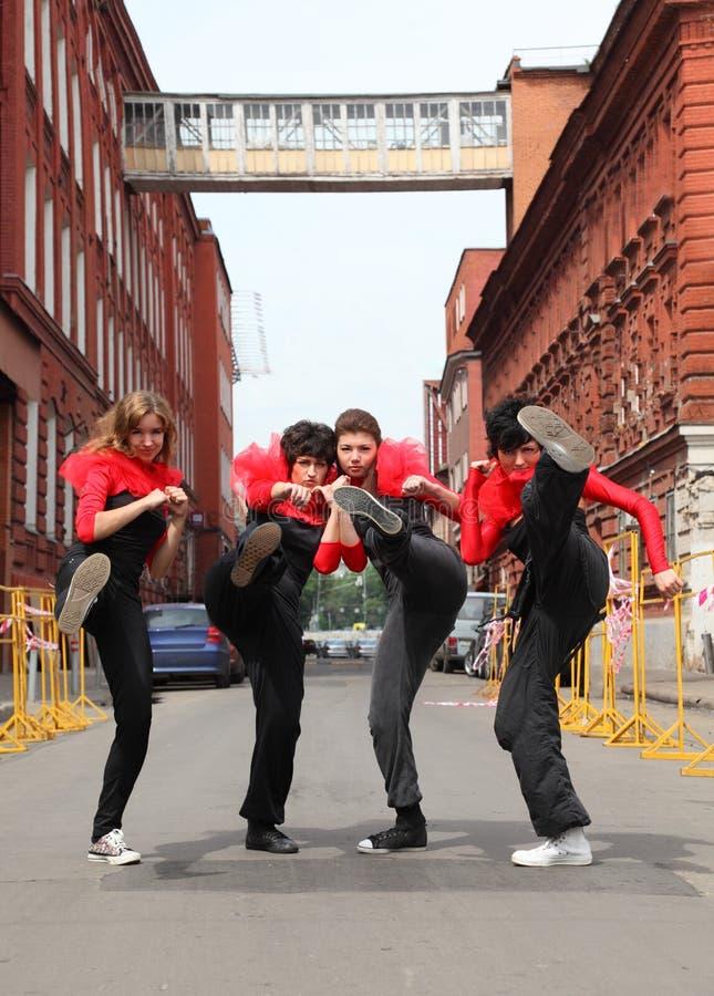 Quattro ragazze che si levano in piedi sulla via immagini stock
