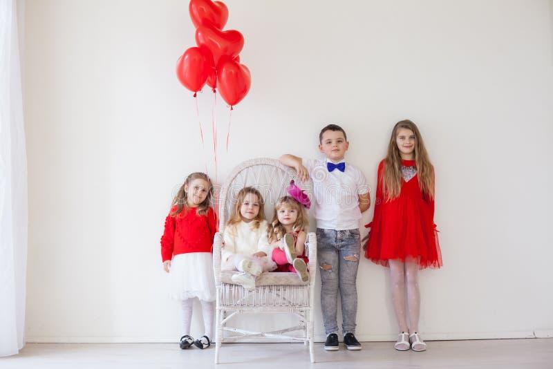 Quattro ragazze e un ragazzo in una stanza bianca con palloncini rossi fotografie stock