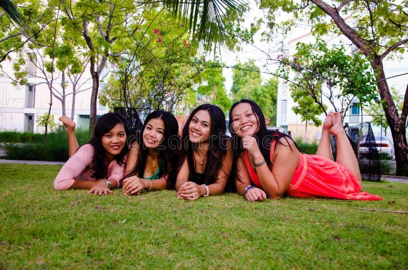 Quattro ragazze indonesiane felici si riposano su erba fotografie stock libere da diritti