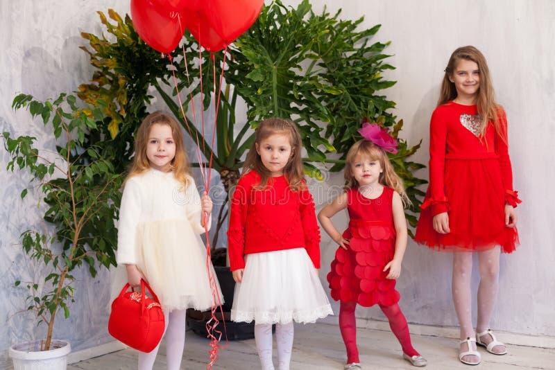 Quattro ragazze in una stanza bianca con palloncini per le vacanze rosse immagini stock