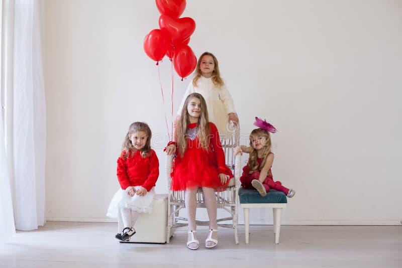 Quattro ragazze in una stanza bianca con palloncini per le vacanze rosse fotografie stock libere da diritti