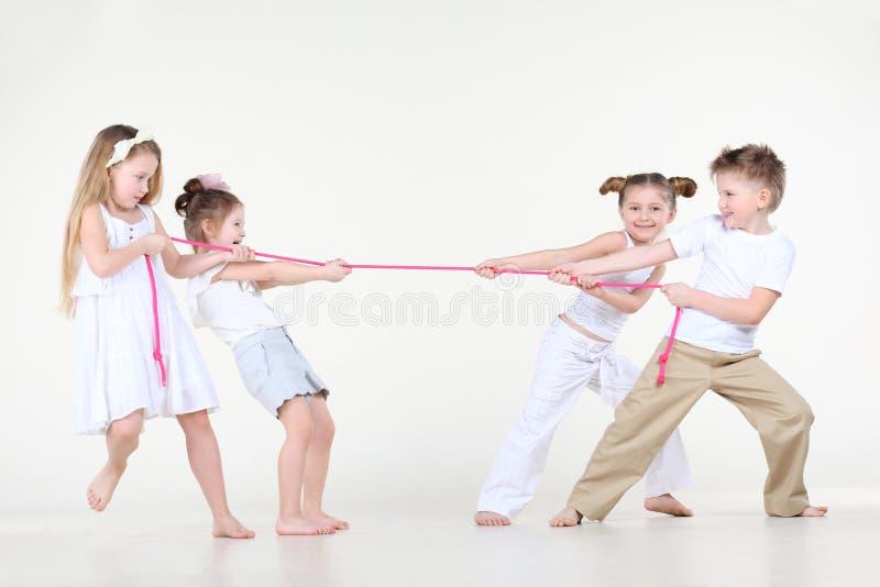 Quattro ragazzino e ragazze nel bianco stringono la corda eccessivamente rosa. fotografia stock libera da diritti