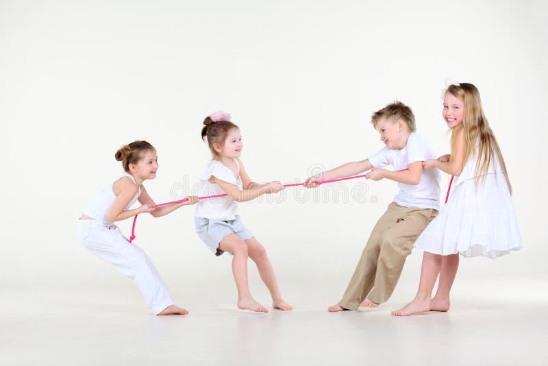 Quattro ragazzino e ragazze in vestiti bianchi dissipano sopra la corda fotografie stock libere da diritti