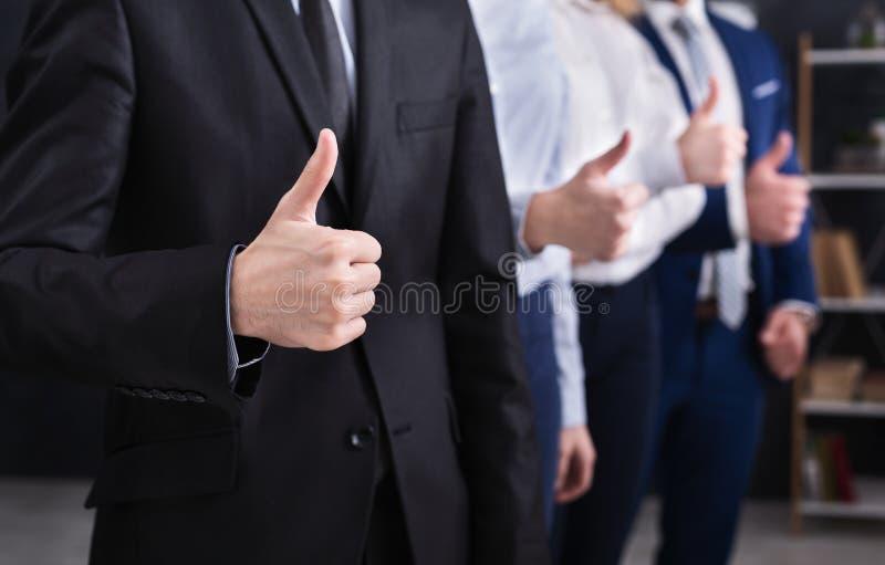 Quattro riusciti uomini d'affari che mostrano i pollici su nell'ufficio immagini stock libere da diritti