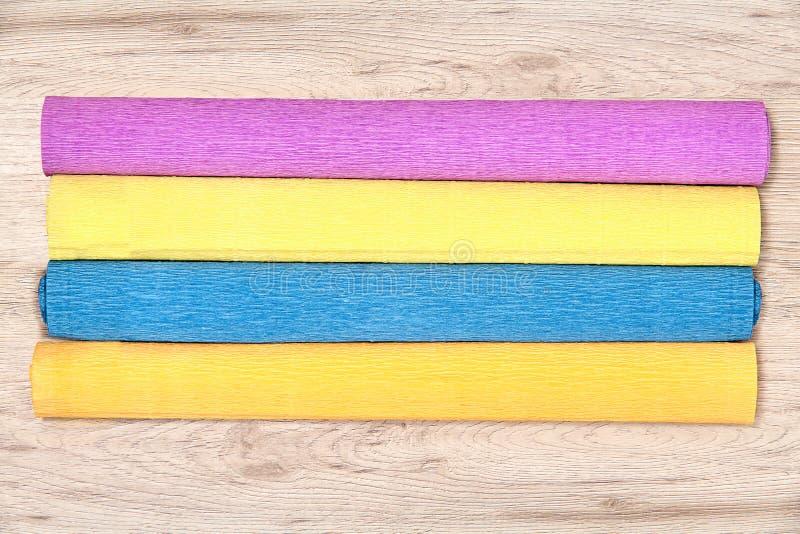 Quattro rotoli colorati differenti della carta crespa sono a bordo fotografia stock