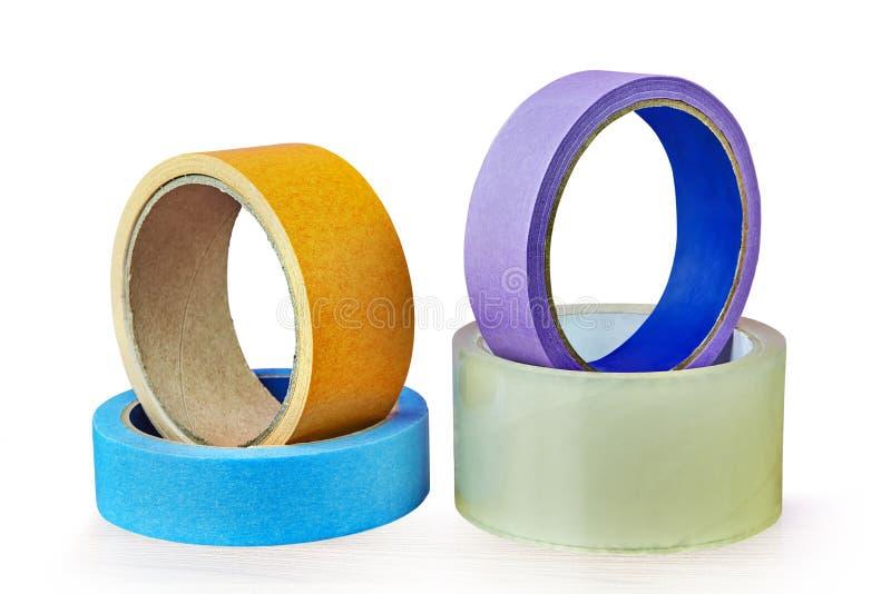 Quattro rotoli del nastro adesivo che si trovano sulla tavola, fondo bianco fotografia stock libera da diritti