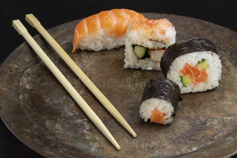 Quattro rotoli di sushi su un di piastra metallica scuro, con i bastoncini fotografie stock libere da diritti