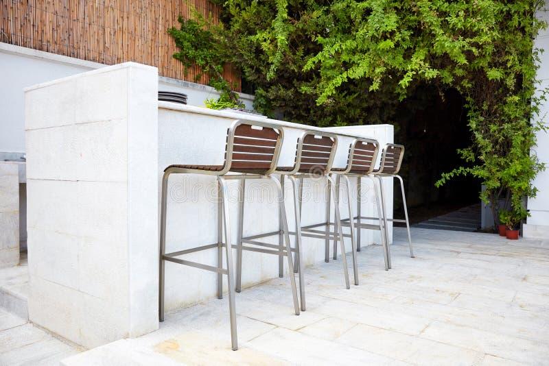 Quattro sedie vuote dello sgabello da bar con i sedili di legno e piede del metallo vicino ad un contatore concreto bianco della  fotografia stock libera da diritti