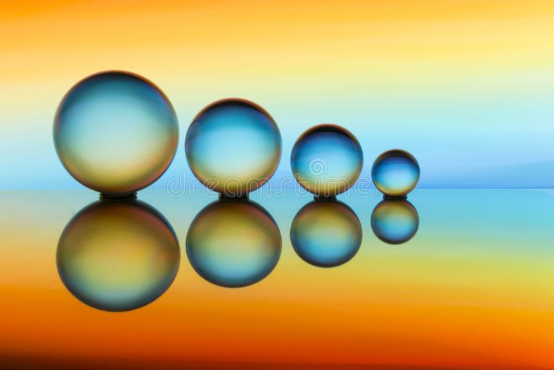 Quattro sfere di cristallo in una fila con le strisce variopinte di colore dell'arcobaleno dietro loro immagine stock libera da diritti