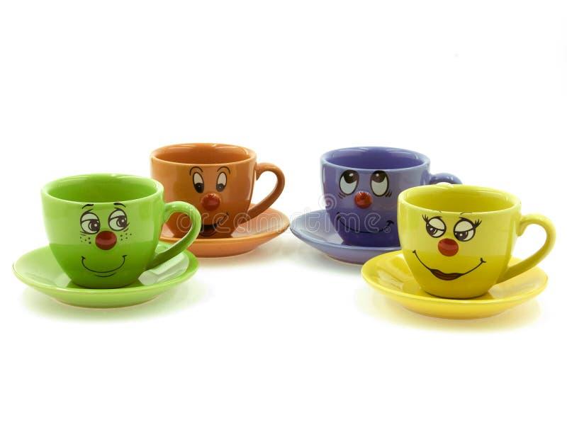Quattro tazze del bambino con i fronti curiosi immagine stock