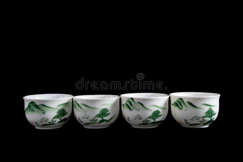 Quattro tazze di tè bianche tradizionale cinese/giapponese messe con il modello verde di scena dell'albero nel fondo nero solido immagine stock