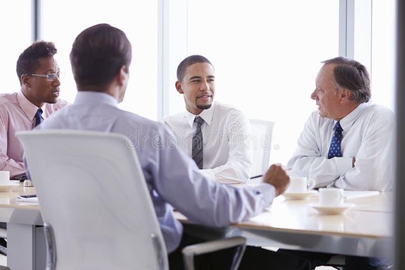 Quattro uomini d'affari che hanno riunione intorno alla Tabella della sala del consiglio immagini stock