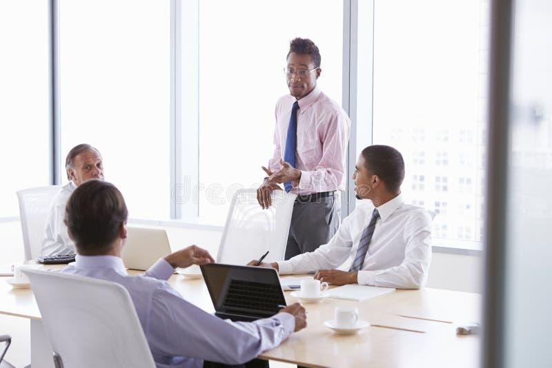 Quattro uomini d'affari che hanno riunione intorno alla Tabella della sala del consiglio fotografia stock libera da diritti