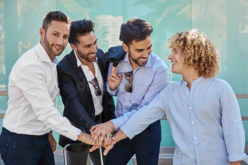 Quattro uomini d'affari che si tengono per mano insieme nel gesto di unità immagine stock libera da diritti