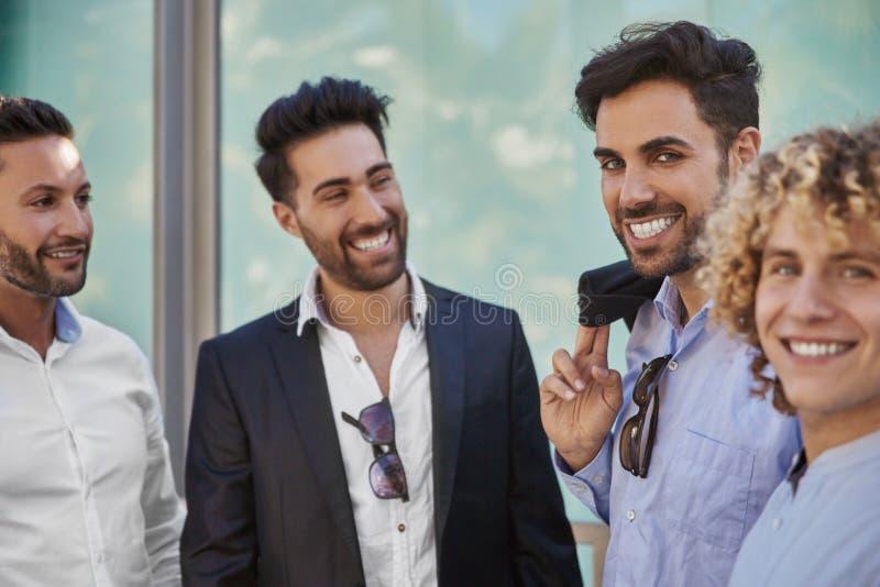 Quattro uomini d'affari felici nel sorridere convenzionale dei vestiti fotografia stock libera da diritti