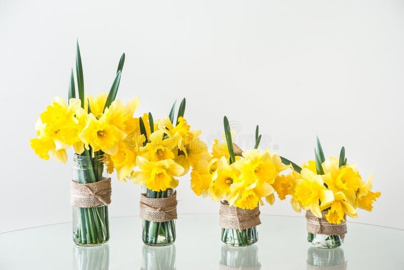 Quattro vasi di vetro con i narcisi gialli luminosi fotografia stock libera da diritti