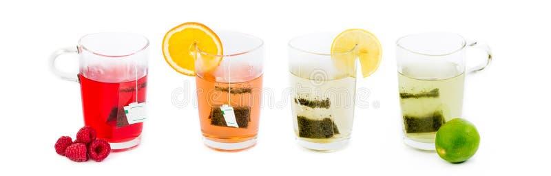 Quattro vetri con il tè della frutta - vari gusti, colori differenti fotografia stock libera da diritti