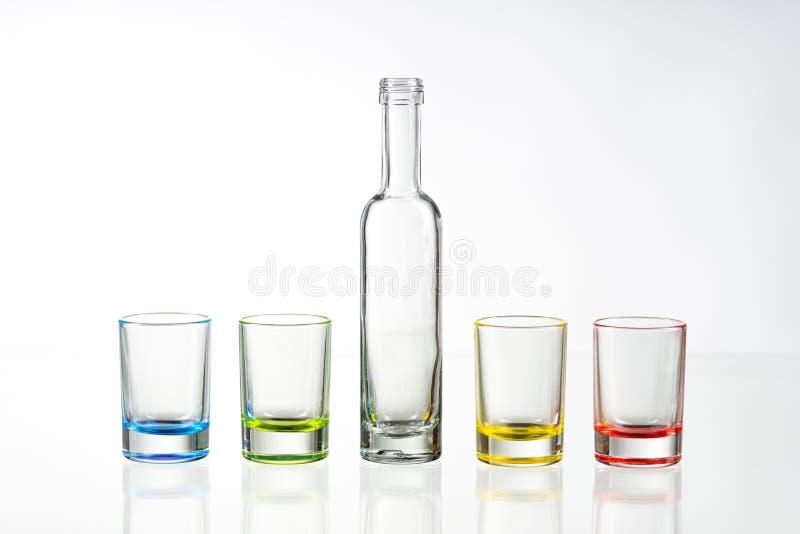 Quattro vetri di colpo vuoti multicolori e la piccola bottiglia hanno disposto lo sym fotografia stock