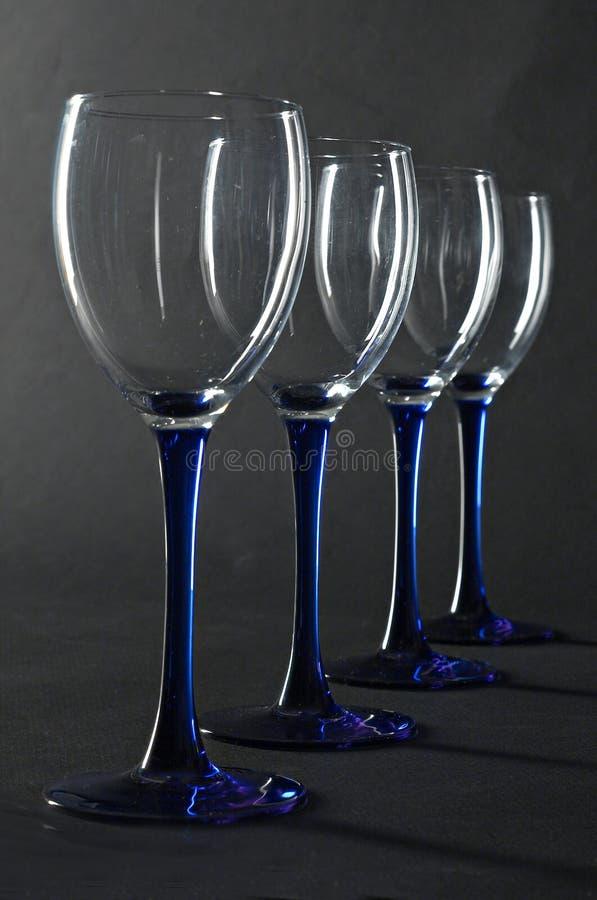 Quattro vetri di vino blu vuoti immagini stock libere da diritti