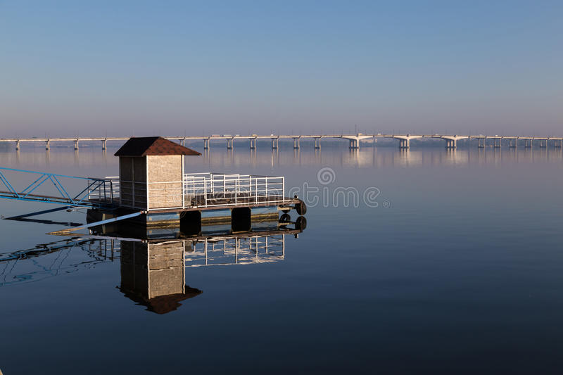 Quay afloat reflected on mirror water surface. At clear summer morning. bridge across the Dnipro river in the background . Dnepropetrovsk. Ukraine stock image