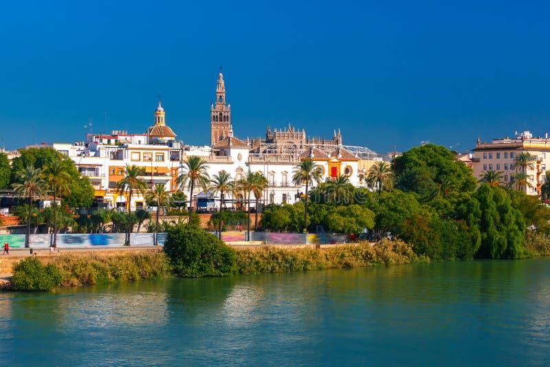 Quay of Guadalquivir and Giralda, Seville , Spain. Quay of the river Guadalquivir, Plaza de toros de la Real Maestranza de Caballeria and Giralda in the sunny royalty free stock photo