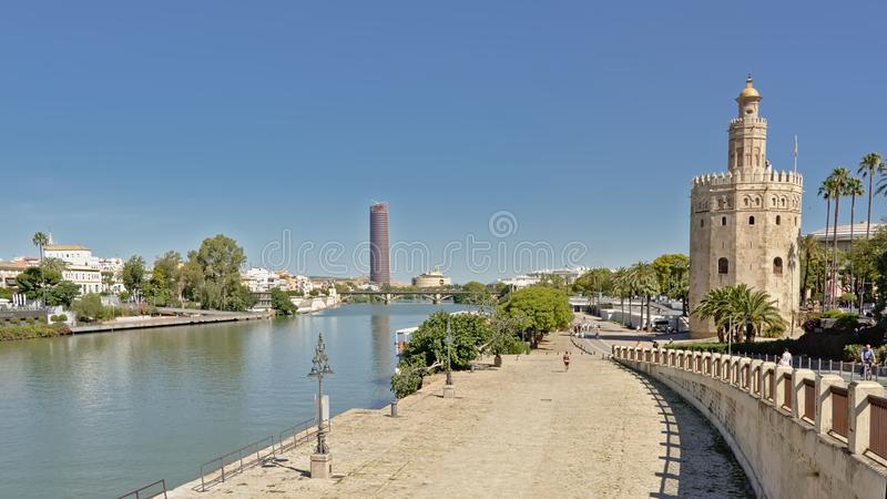 Quays of Guadalquivir river, with historical Torre del Oro, and modern Seville tower. On a sunny day with clear blue sky stock images