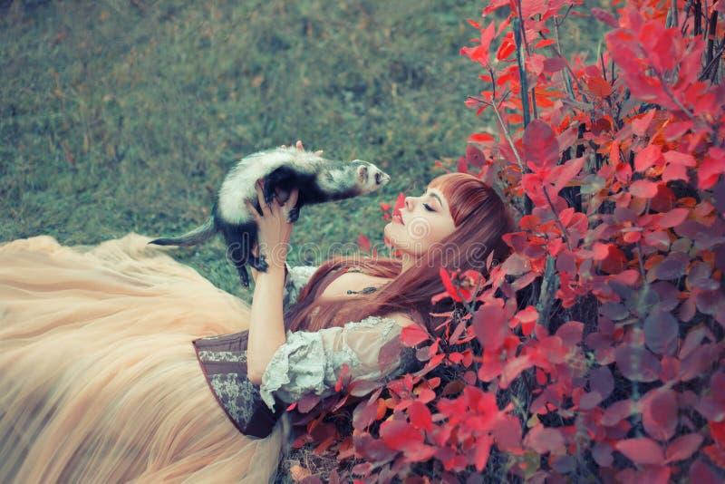Que encanta la belleza mentiras en hierba verde en el bosque, princesa en vestido ligero largo, magnífico juega con un hurón como imagen de archivo libre de regalías