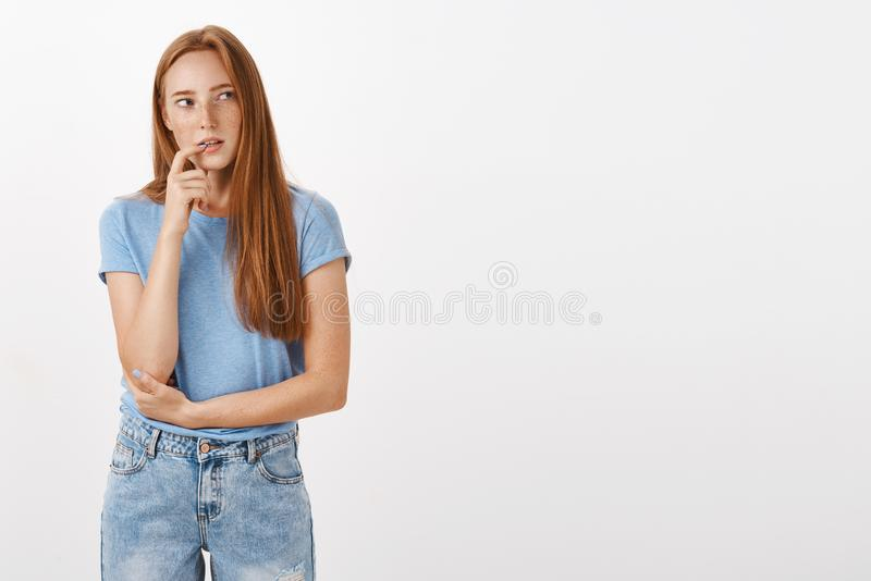 Que se eu peço a comida lixo Mulher concentrada e curiosa pensativa do ruivo no t-shirt e em calças de brim azuis que morde o ded fotos de stock