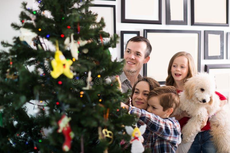 Que sorri membros da família decora a árvore de Natal fotos de stock royalty free
