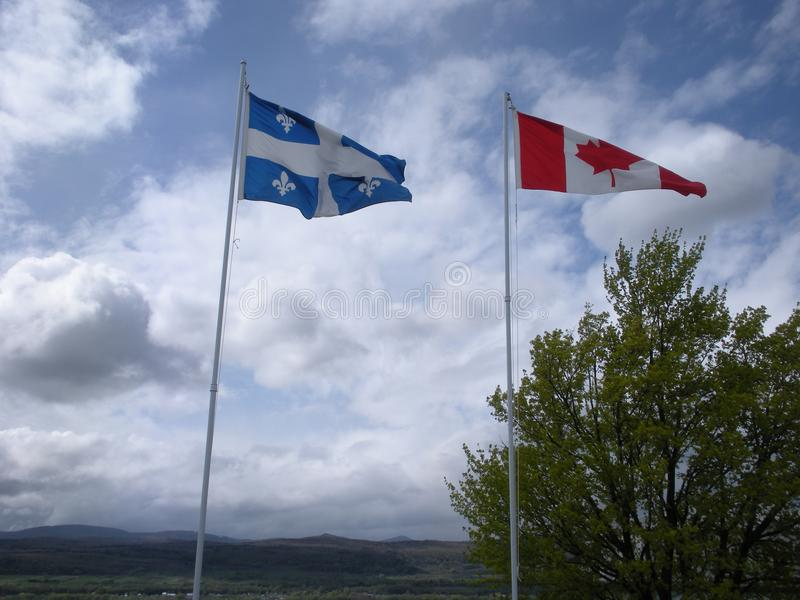 Quebec and Canada Flags Waving in the Wind stock photo