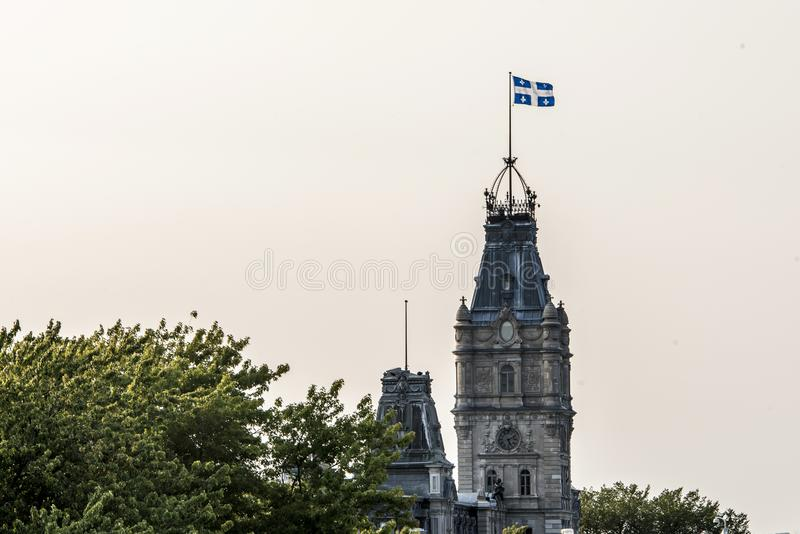 QUEBEC CITY CANADA blue white flag proudly on top of clock tower of parliament building of national assembly of Quebec royalty free stock images