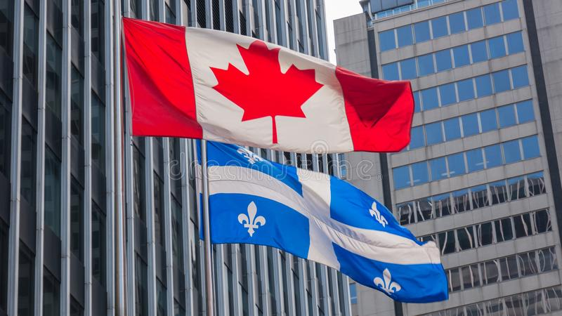 Quebec och Kanada flaggor som tillsammans fladdrar i vinden i centret av Montreal royaltyfri foto