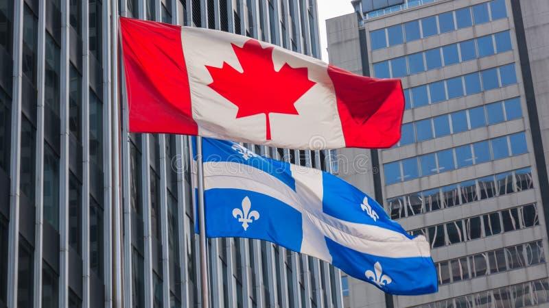 Quebec- und Kanada-Flaggen, die zusammen im Wind im Stadtzentrum von Montreal flattern lizenzfreies stockfoto
