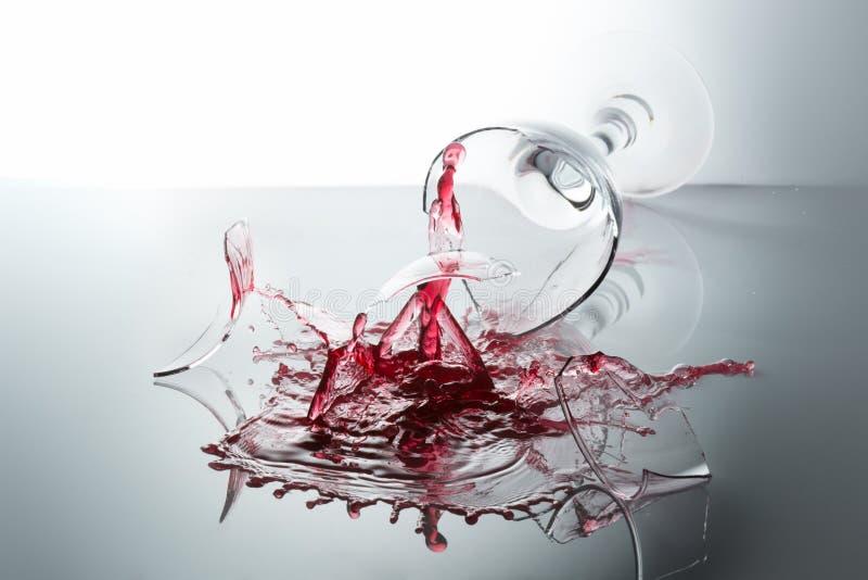 Quebra de um vidro completo do vinho tinto imagem de stock royalty free